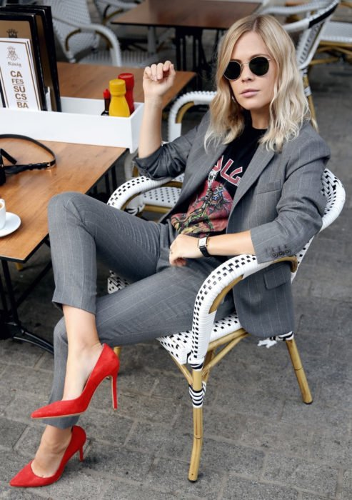 Atuendos formales y juveniles para oficina; mujer rubia sentada en restaurante, con traje sastre gris, playera rockera, lentes de sol y zapatillas rojas