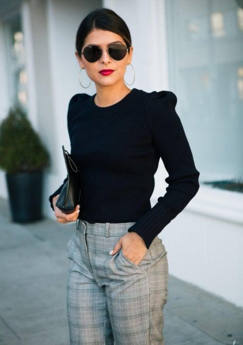 Atuendos formales y juveniles para oficina; mujer con lentes de sol, blusa negra con hombreras, pantalón gris a cuadros