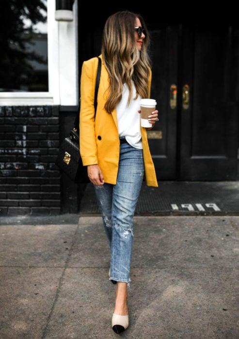 Atuendos formales y juveniles para oficina; mujer caminando en la calle con su café, saco amarillo canario y jean desgastado