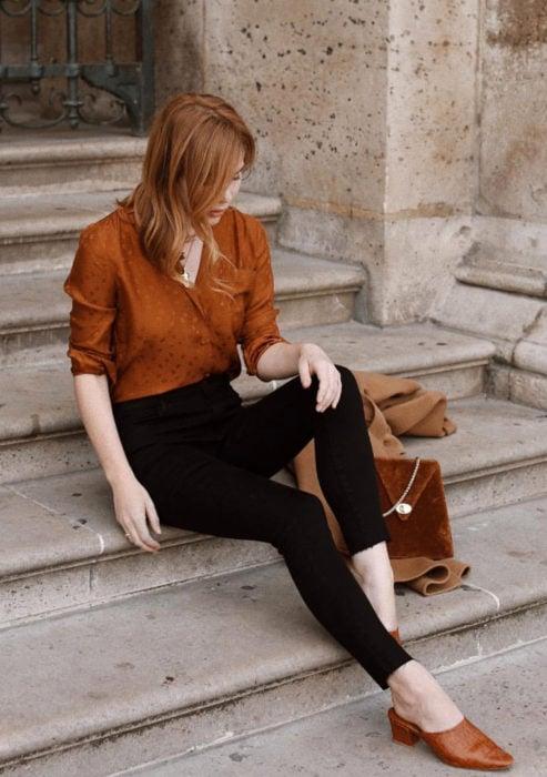 Atuendos formales y juveniles para oficina; mujer pelirroja sentada en las escaleras con blusa anaranjada y pantalones entubados