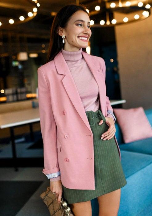 Atuendos formales y juveniles para oficina; mujer con blusa cuello de tortuga, saco rosa, falda verde