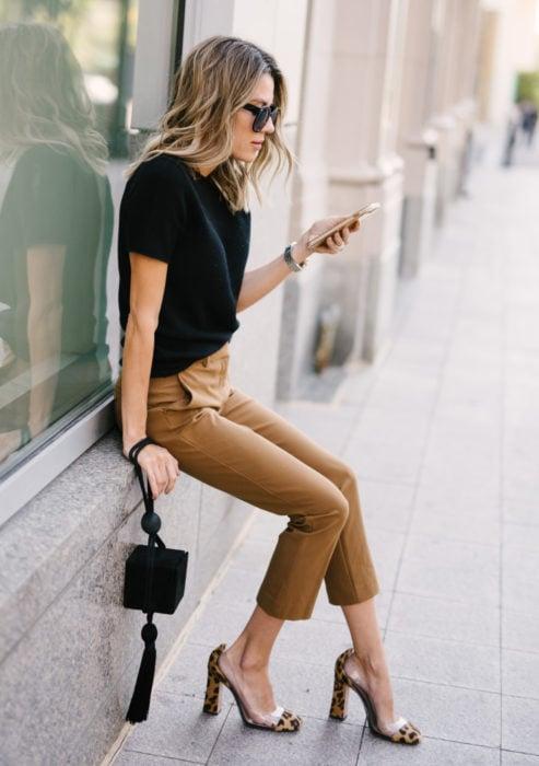 Atuendos formales y juveniles para oficina; mujer sentada en la calle, con lentes de sol, blusa negra, pantalones caqui y zapatos mule con animal print de leopardo