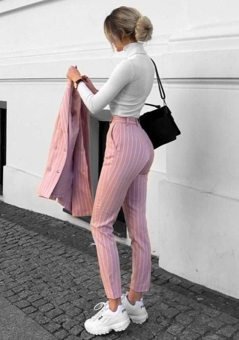 Atuendos formales y juveniles para oficina; mujer rubia peinado de chongo bajo, blusa blanca cuello de tortuga, pantalón rosa y saco color rosa con rayas y tenis blancos Fila