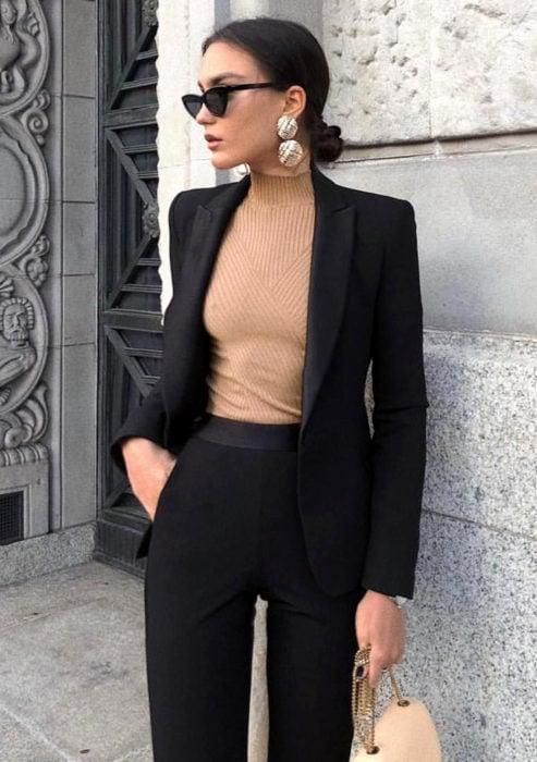 Atuendos formales y juveniles para oficina; mujer con lentes de sol, blusa café, saco y pantalón de vestir