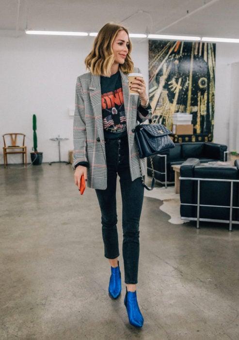 Atuendos formales y juveniles para oficina; saco de cuadros, playera de rock, jeans entubados, botines azul eléctrico