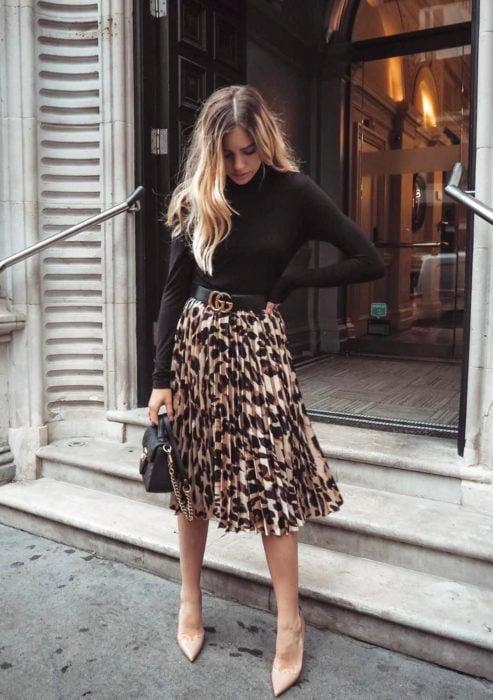 Atuendos formales y juveniles para oficina; mujer de cabello rubio, blusa de mangas largas negra, falda de animal print de leopardo, zapatillas nude y bolsa de mano
