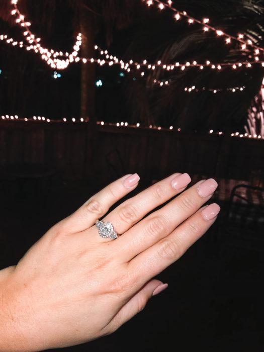 Chica mostrando su anillo de compromiso, anillo de plata con diamante