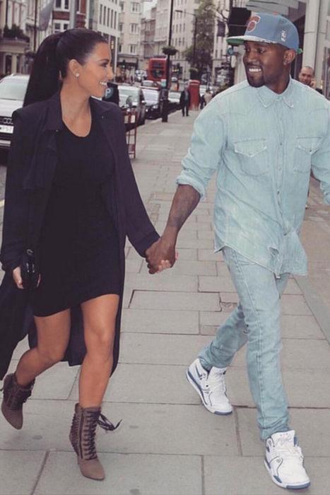 Kim Kardashian y Kanye West tomados de las manos mientras caminan por la calle