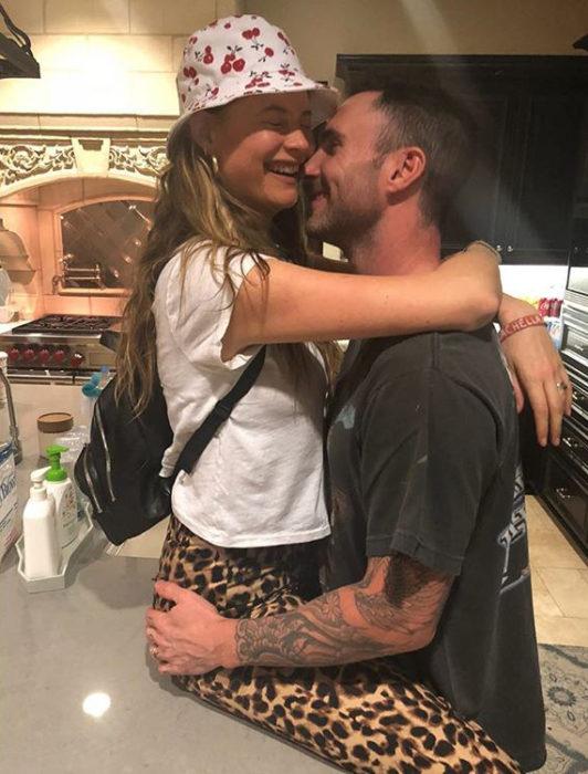 Adam Levine y Behati Prinsloo abrazados mientras están en la cocina de su casa