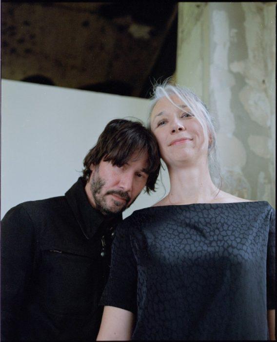 Keanu Reeves y Alexandra Grant abrazados mientras están en una galería