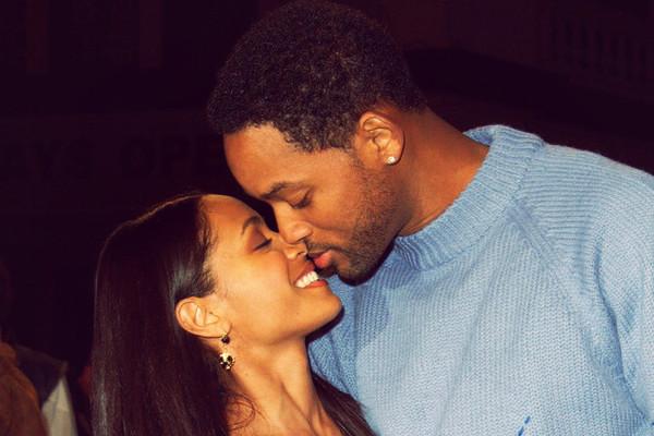 Will Smith y Jada Piket besandose mientras están en una alfombra roja