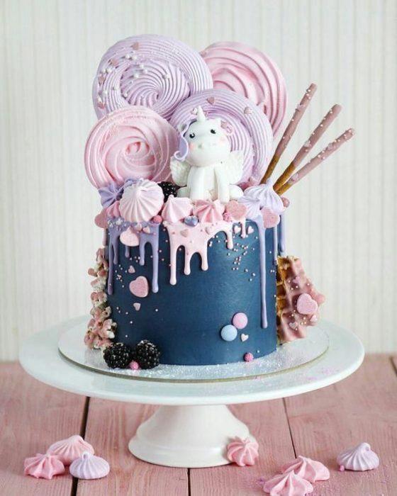 Pastel de betún de zarzamora con dulces de betún en colores rosa y lila