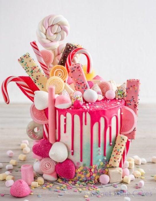 Pastel con betún blanco y chorreado de fresa con caramelos