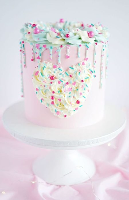 Pastel alto de vainilla con betún de fresa y decorado con caramelos de colores