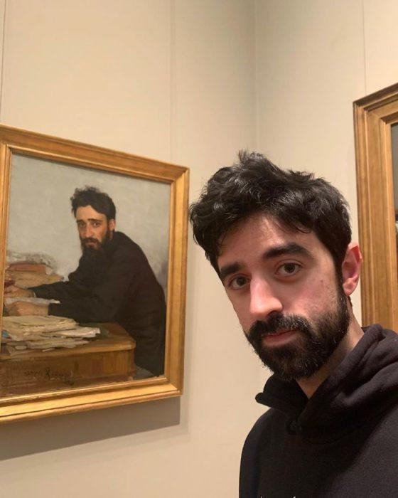 Hombre tomando una selfie frente a una pintura de la edad media