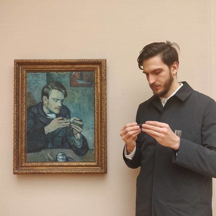 Hombre revisando su teléfono celular junto a una pintura