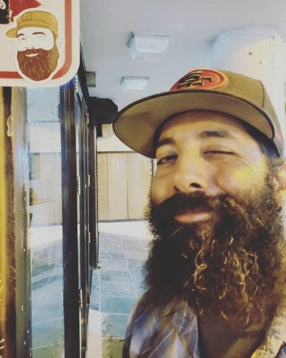 Hombre sonriendo junto a una etiqueta de un chico con barba larga y abultada