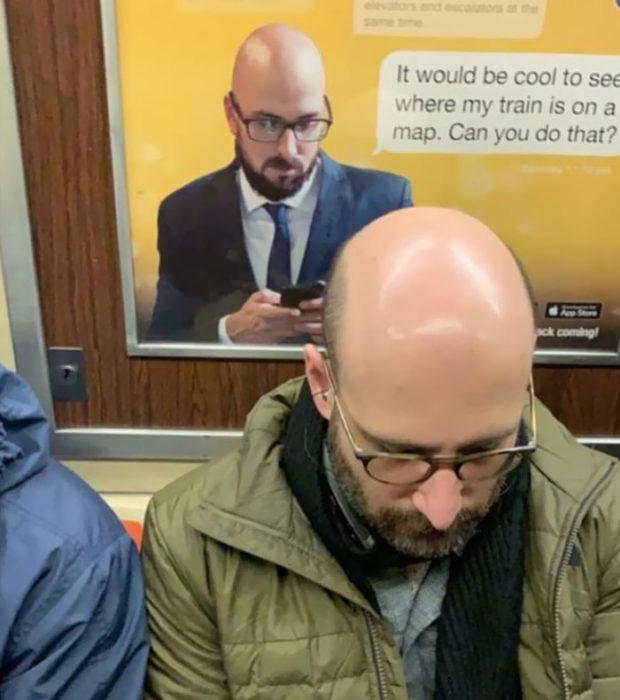 Hombre sentado frente a una ventanilla con un homrbe checando su teléfono celular