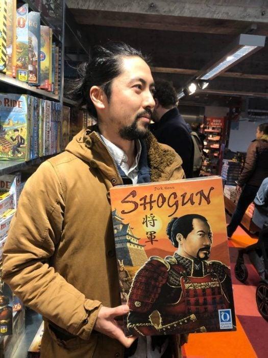 Hombre con rasgos asiáticos sosteniendo un libro japones