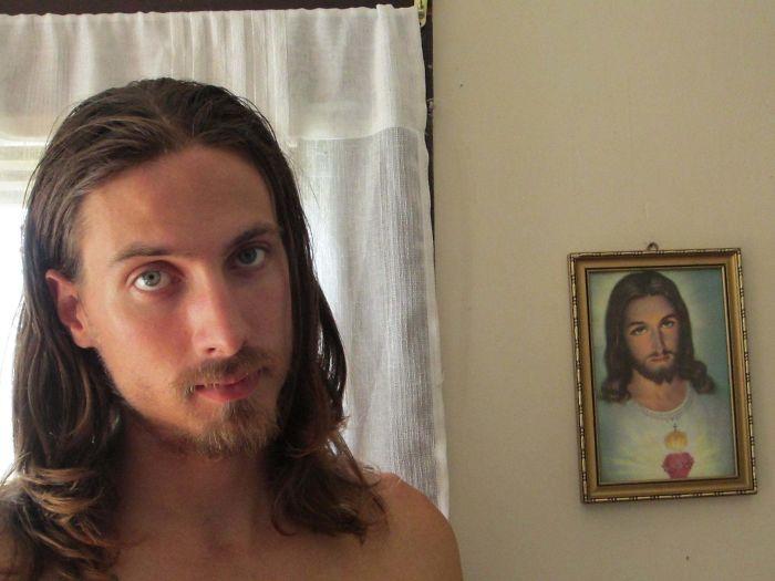 Chico con cabello largo posando junto a la imagen de Cristo