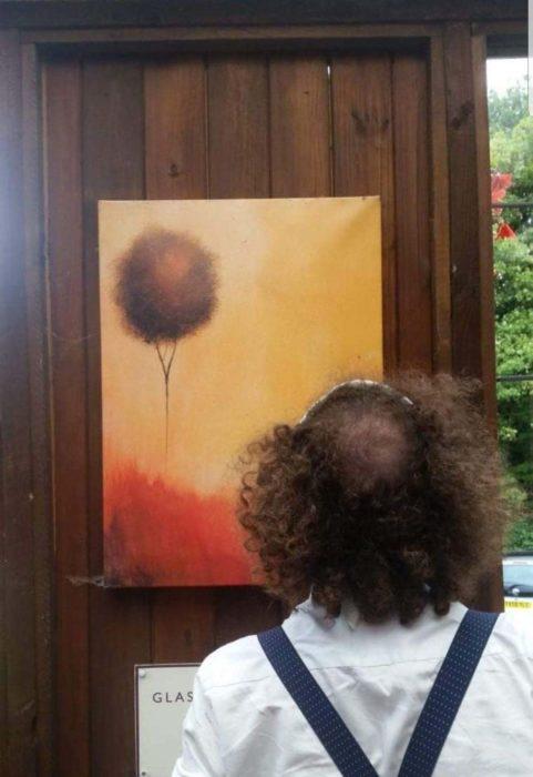 Hombre de espaldas admirando una pintura de un globo en el atardecer
