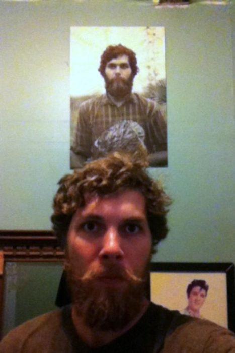 Chico posando frente a una fotografía de un hombre desconocido
