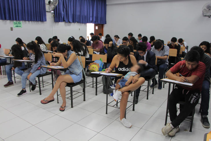 Chica sosteniendo en brazos a su bebé mientras contesta un examen en una aula de escuela