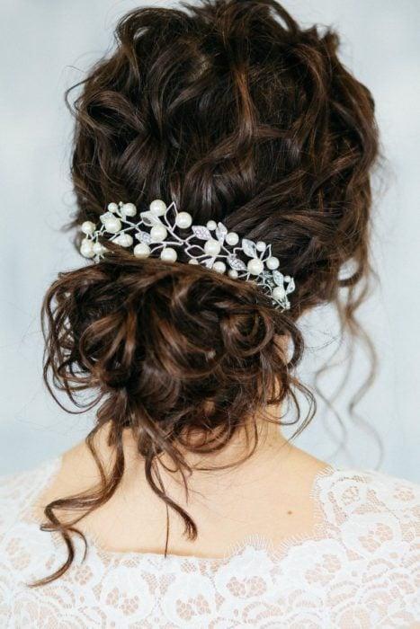 Peinado para novia de cabello rizado en recogido bajo con adorno de tocado con perlas