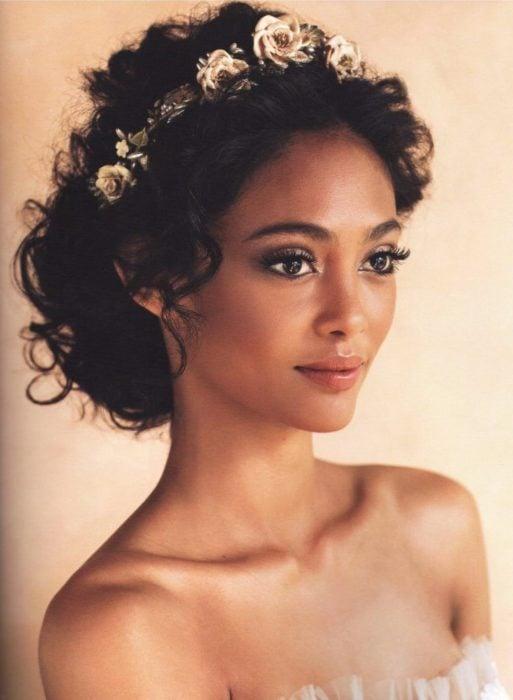 Recogido bajo con corona de flores, peinado para novias de cabello rizado