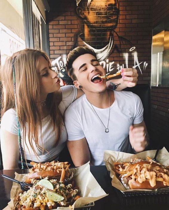 Pareja de novios comiendo papas fritas y hamburguesas