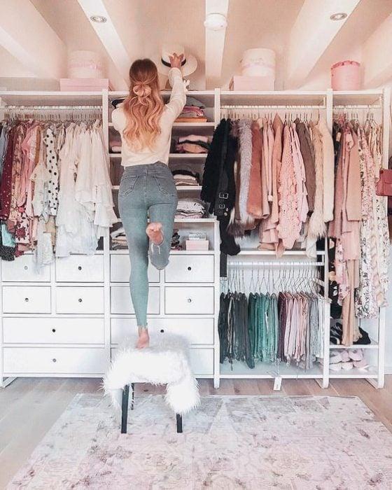 Chica sobre una silla revisando su armario