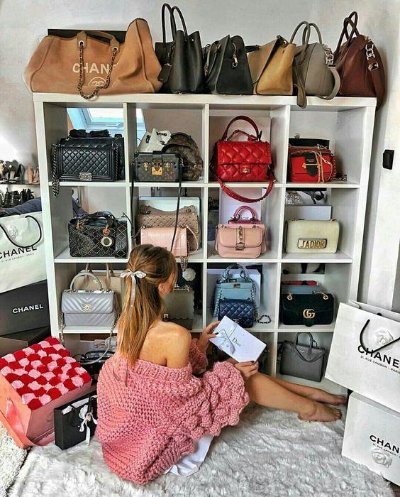 Chica sentada frente a un armario repleto de bolsos de colores