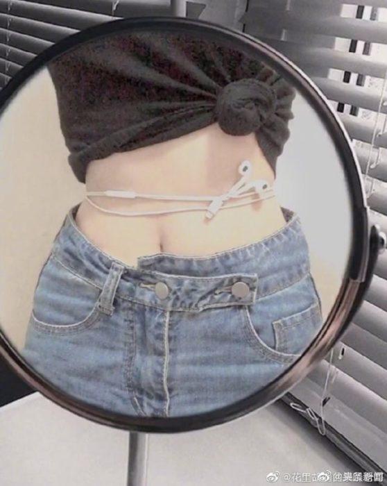 Chica midiendo el tamaño de su cintura con el cordón de los audífonos