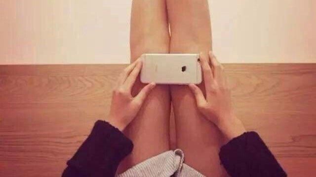Chica midiendo el tamaño de sus piernas con un iphone 6