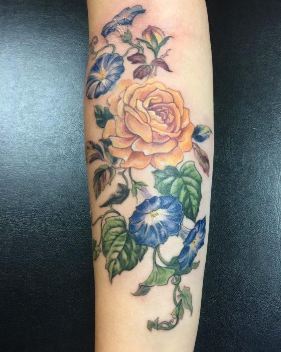 Tatuaje de rosa amarilla y flores azules