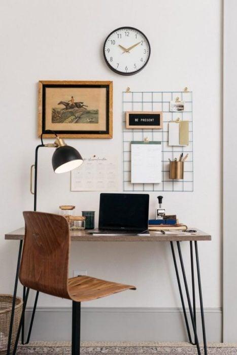 Área de escritorio con mesa y silla de madera con soporte de metal