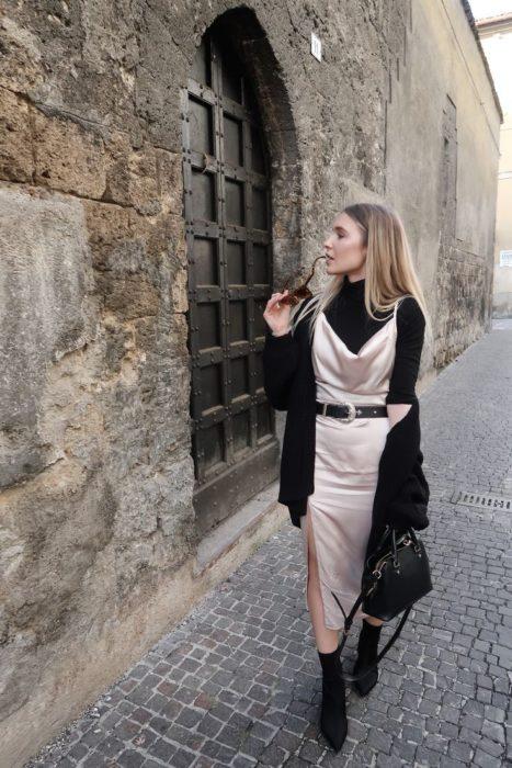 Slip dress color crema con ensamble y botines negros, y un suéter negro debajo