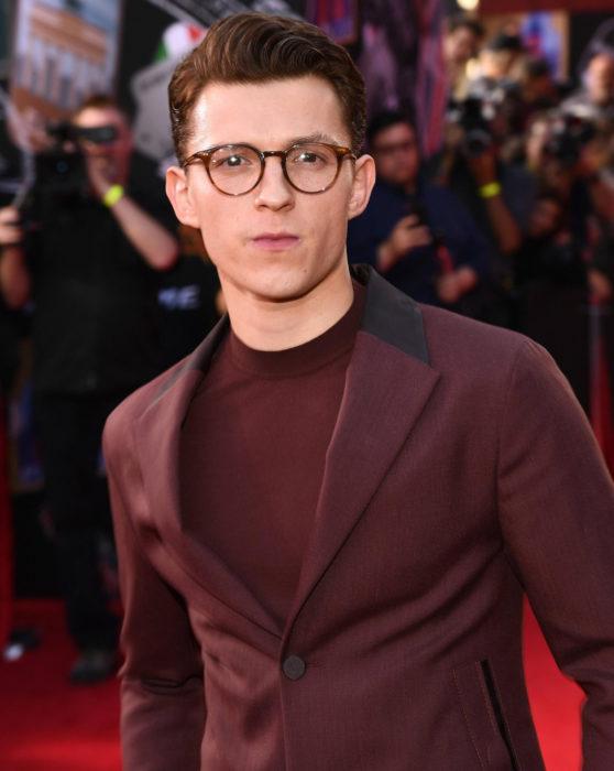 Tom Holland con traje de gala color vino y lentes; Spider-Man se unirá a comunidad LGBT+