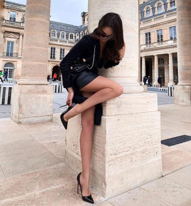 Chica utilizando tacones negros, recargada en un pilar