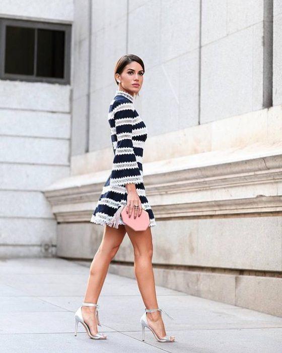 Mujer usando tacones color plata y vestido con estampado rayado