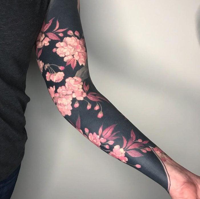 Tatuaje tipo manga con fondo negro y flores rosadas