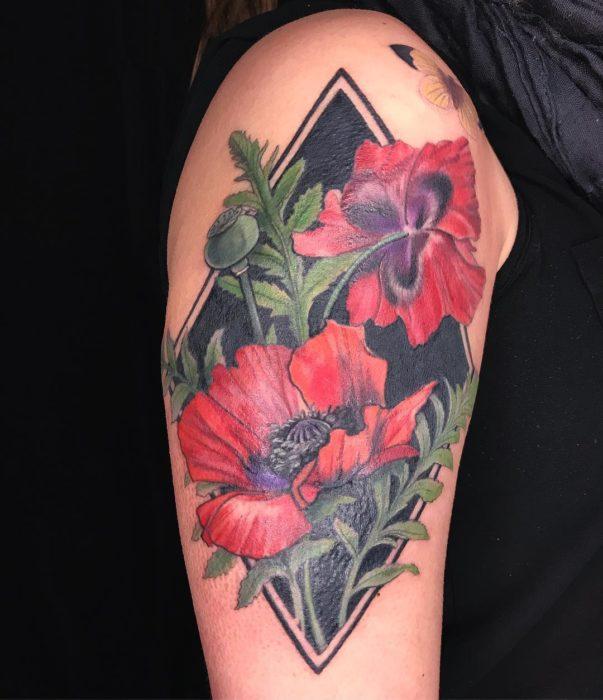 Tatuaje de flores rojas, con fondo negro de un rombo con una mariposa amarilla