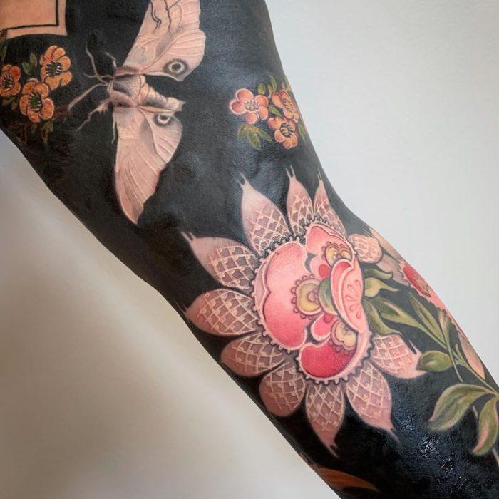 Tatuaje con fondo negro con flor y mariposa