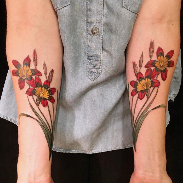 Tatuajes de flores rojas en ambos antebrazos
