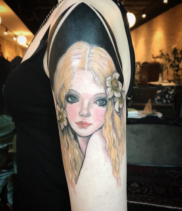 Tatuaje sobre brazo de rostro de mujer rubia