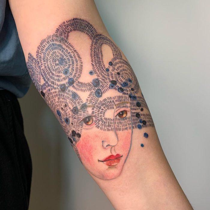 Tatuaje sobre antebrazo de un rostro y 'pensamientos'