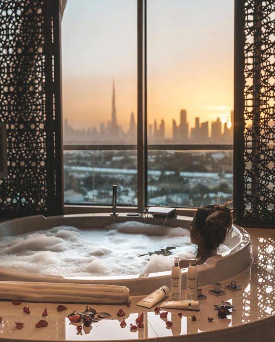 Chica en tina de baño mirando el atardecer