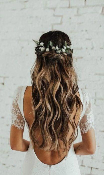 Peinado para novia de cabello rizado suelto con tocado floral