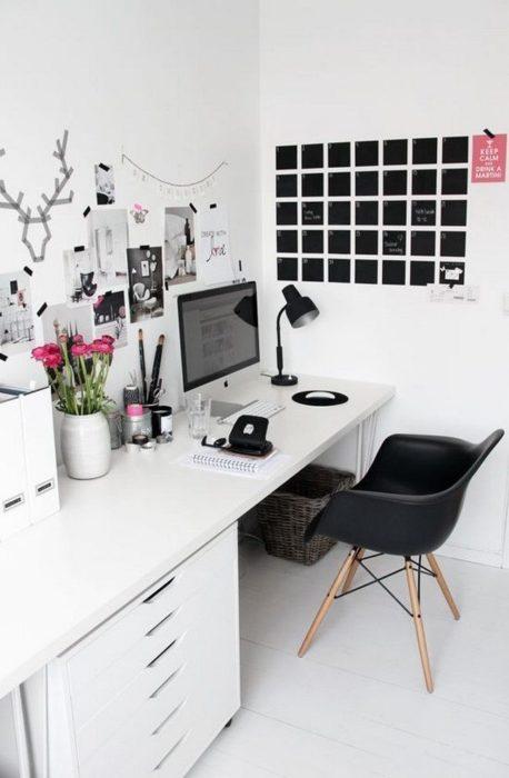 Escritorio blanco y paredes del mismo color, silla negra al igual que el calendario que hacen mach perfecto