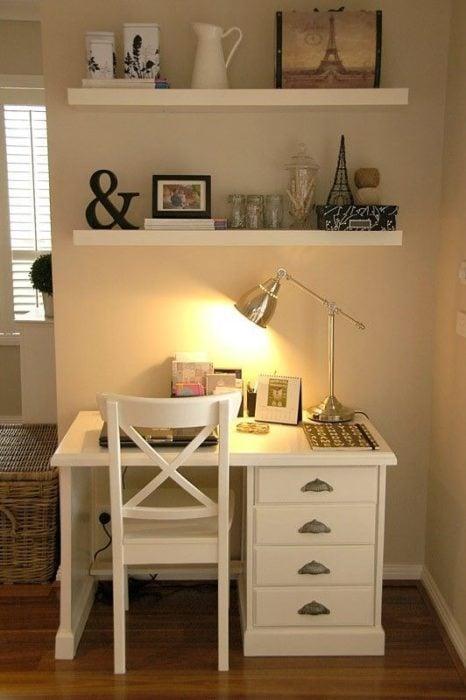 Área de trabajo con luz amarilla, con muebles blancos, y repisas con adornos